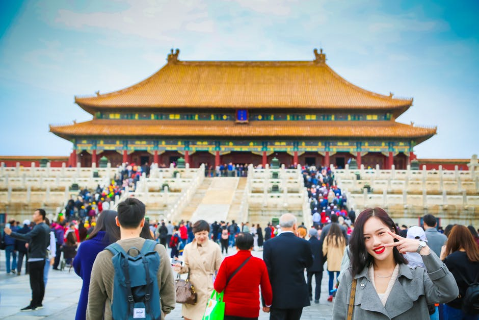 A group of people standing in front of Forbidden City