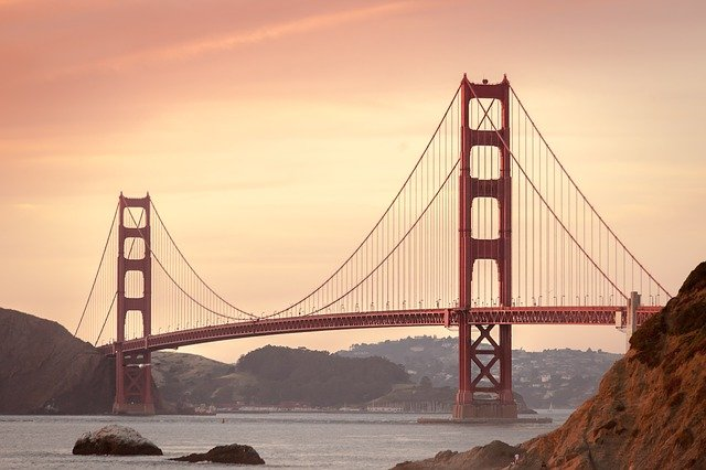 A large bridge over a body of water with Golden Gate Bridge in the background