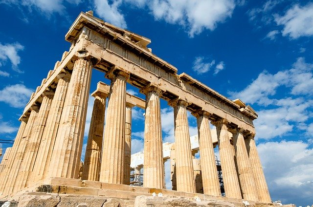 A large tall tower with a clock on the side of Parthenon